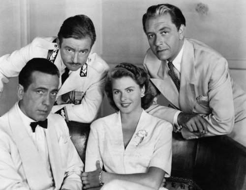 "A promotional still featuring cast members from ""Casablanca"". Included in the photo are Humphrey Bogart, Claude Rains, Ingrid Bergman, and Paul Henreid"