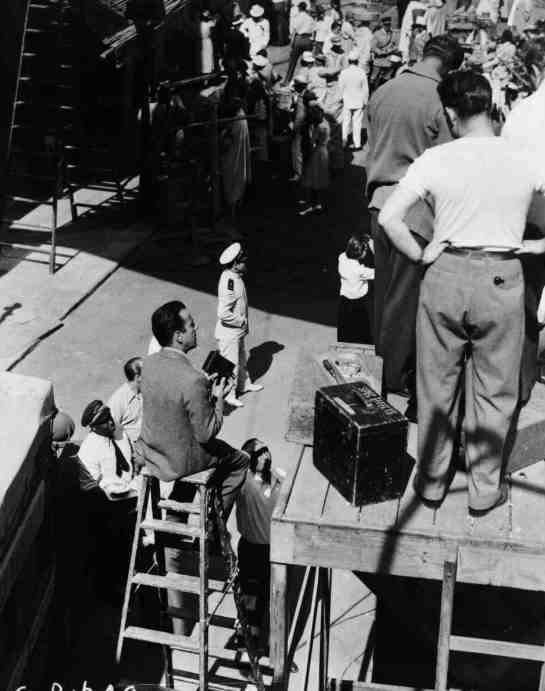 This interesting photo captures Bogart sitting on a tall ladder making some home movies of his experience on set.
