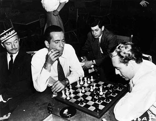 "Cast members of ""Casablanca"" were known to spend down time enjoying competitive games of chess. In fact, it is said that while watching Bergman play, Bogart uttered ""Here's looking at you"", a phrase that he would bring into the movie via improvisation. Of course that line would become one of the film's many memorable quotes."