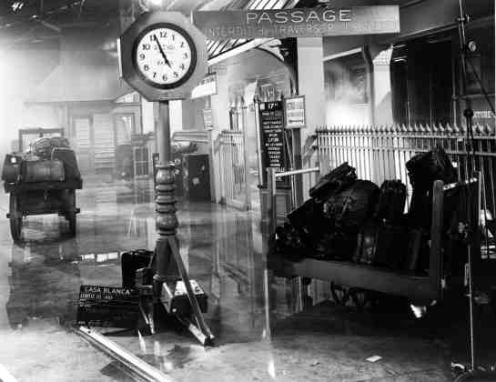 This is a studio set still of the Paris train station. The scene is important to the story as it reveals why Rick has become so callous and distant. The scene at the train station takes place as the Nazi's are preparing to enter Paris. The chaotic flow of people trying to leave the city and the mood-setting downpour of rain helped give the scene its amazing life.